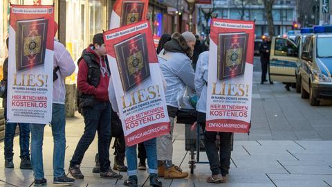"""Männer mit Plakaten der salafistischen """"Lies!""""-Aktion auf der Frankfurter Zeil"""