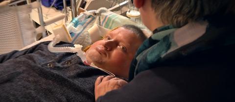 Der Locked-in-Syndrom-Patient Gerhard Stoll in seinem Krankenbett (mit Krankenschwester Sigrid Achenbach)