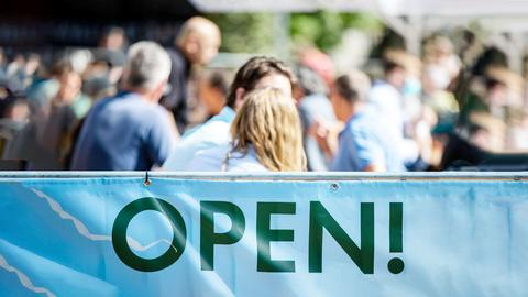 """Menschen sitzen in der Außengastro, davor ein Schild mit der Aufschrift """"Open!"""""""