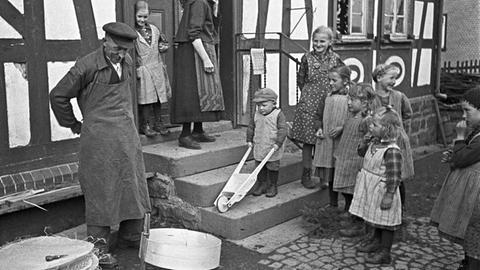 30er Jahre: Ein Siebmacher bei der Arbeit vorm Haus