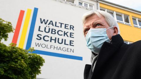Ministerpräsident Volker Bouffier läuft im Vordergrund mit einem Nasen-Mund-Schutz vorbei. Im Hintergrund ist an der gelben Fassade der Schule ein mehrere Stockwerke hohes Plaktat zu sehen. Darauf die Aufschrift: Walter Lübcke-Schule Wolfhagen.