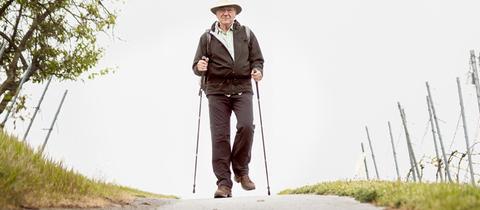 Gunter Lutzi mit Stöcken auf einem Weg durch Weinberge wandernd.