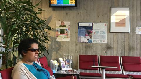 Lydia Zoubek sitzt mit dem Zettel einer Wartenummer im Wartebereich des Rathauses. Die Nummern werden auf einem Monitor angezeigt.