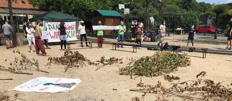 Demonstranten, die Plakate gegen den Autobahnausbau hochhalten. Auf dem Boden liegen vertrocknete Äste