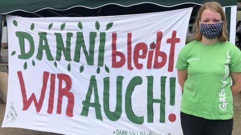 """Eine junge Frau mit Gesichtsmaske neben dem Plakat """"Danni bleibt - wir auch"""""""