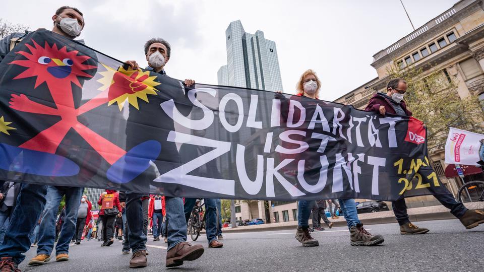 """1.Mai in Frankfurt: Menschen mit einem Transparent mit dem Motto """"Solidarität ist Zukunft"""" laufen an der Zentrale der Deutschen Bank vorbei."""