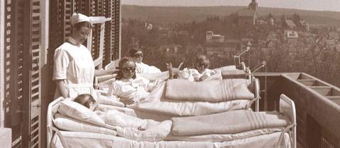 Historische Schwarz-Weiß-Aufnahme von Kindern, die in Krankenbetten auf einem Balkon liegen
