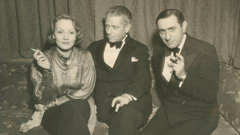Hollywoodstar Marlene Dietrich mit Max Reinhardt und Ernst Lubitsch auf einem Sofa