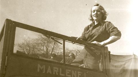 Marlene Dietrich steht in einem US-Jeep