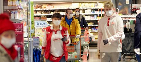 Kunden eines Supermarkts tragen Schutzmasken