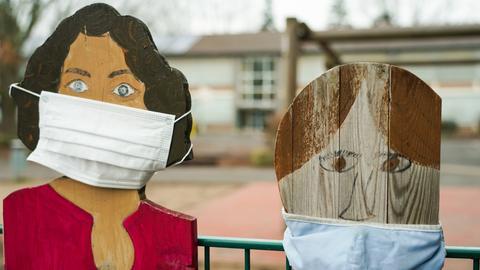 Masken zieren die Figuren am Zaun der Karl-Treutel Grundschule in Kelsterbach.