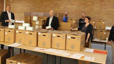 Mitarbeiter des Werra-Meißner-Kreises packen 22.000 OP-Masken in Kisten.