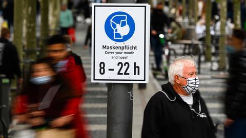 """Ein Mann steht mit Maske neben einem Hinweisschild """"Maskenpflicht"""" auf der Zeil in Frankfurt."""