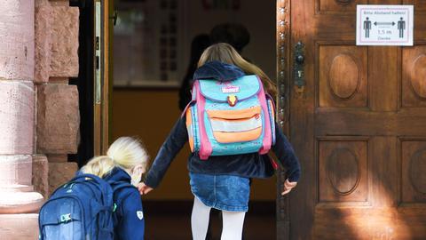 Zwei Kinder betreten ein Schulgebäude