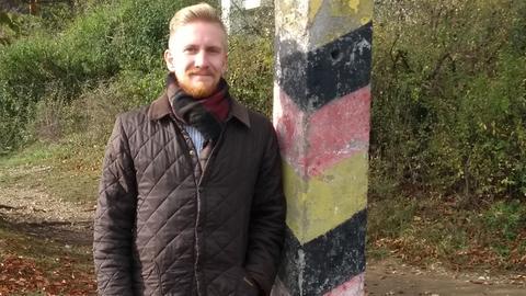 Arndt Macheledt, Historiker in der Gedenkstätte Point Alpha, an einem schwarz-rot-goldenen Grenzstein an der früheren innerdeutschen Grenze