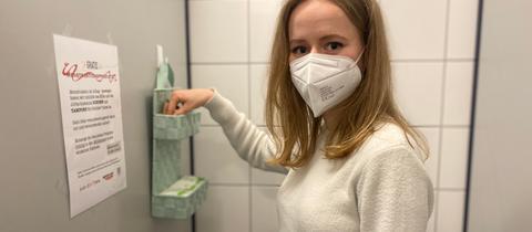 Liah Kaiser zeigt auf der Toilette Körbchen mit kostenlosen Menstruationsartikeln