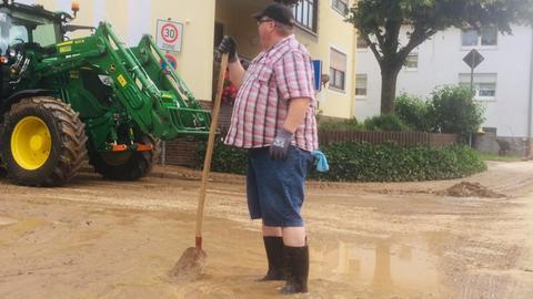 Überschwemmung in Merzhausen - ein Mann mit Schaufel steht mit seinen Gummistiefeln bis zu den Knöcheln in einer schlammbedeckten Straße.