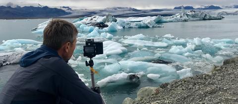 Michael Gutsche mit Kamera vor einem Gletscher.