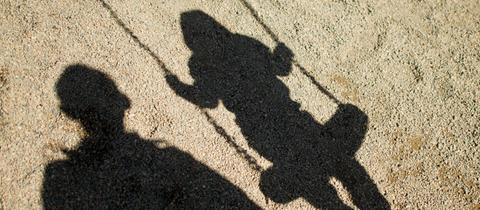 Schatten eines schaukelnden Kindes.