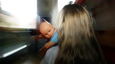 Mädchen von hinten mit Puppe im Arm