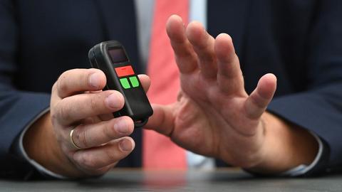 Eine Hand hält ein mobiles Alarmgerät. Es ist schwarz, cirka zehn Zentimeter hoch und hat einen roten und zwei grüne Knöpfe.