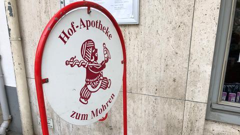 """Aufsteller mit dem Titel """"Hofapotheke zum Mohren"""" und dem Logo, das ein kleines Männchen mit dicken Lippen, großen Ohrringen, Turban, Apothekerstab"""