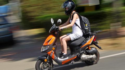 Eine junge Frau fährt mit ihrem Moped