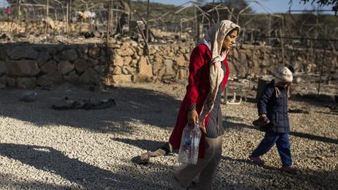 Frau und Kind laufen durch das ausgebrannte Lager in Moria