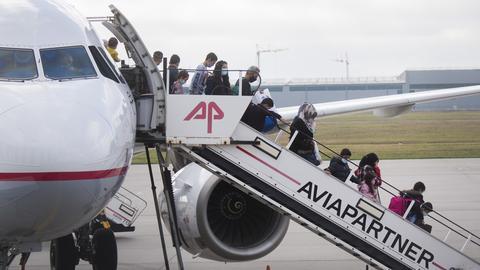 Migranten steigen aus einem Flugzeug am Flughafen Hannover.