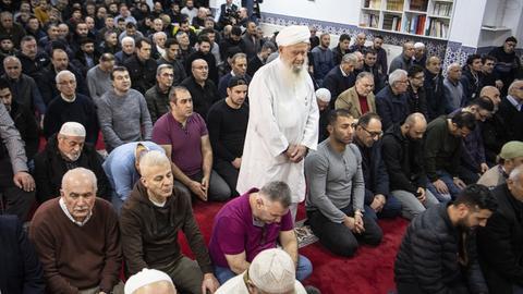 Freitagsgebet in einer Hanauer Innenstadt-Moschee zwei Tage nach dem Anschlag von Hanau. Männer knien auf einem roten Teppich, ein weiß gekleideter Imam steht in ihrer Mitte.