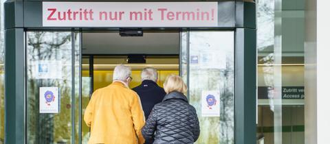 Zwei Männer und eine Frauen laufen in ein Impfzentrum in Hessen.