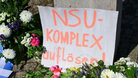 """""""NSU-Komplex auflösen"""" steht auch einem Karton, der inmitten das Blumenmeer an einem Gewdenkort gestellt wurde."""