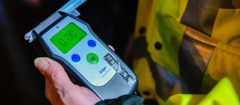Ein Atemalkoholtest-Gerät in der Hand eines Polizisten, dessen Anzeige 0,0 Promille anzeigt.