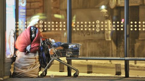 Eine Obdachlose sitzt eingehüllt in Schlafsäcke an einer Bushaltestelle