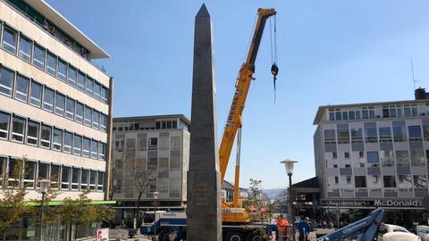 Arbeiter stellen in Kassel das 16 Meter hohe Kunstwerk auf.