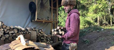 Marc Freukes mit Brennholz vor seiner Jurte im Odenwald