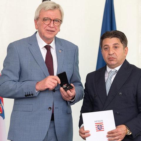 Ministerpräsident Bouffier mit Niculescu Păun, dem Vater des getöteten Vili Viorel Păun. Daneben eine Porträt-Skizze des Anschlagsopfers.