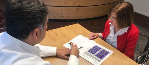 Osteoporosepatien Margit Weimer bespricht mit ihrem Arzt am Schreibtisch ihre Untersuchungsergebnisse.