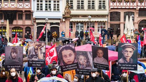 Ostermarsch-Kundgebung auf dem Frankfurter Römerberg: Teilnehmer der Demo halten Plakate mit Portraits von Kriegsopfern hoch.
