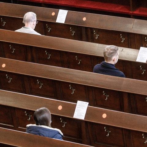 Drei Gläubige sitzen mit Sicherheitsabstand im Gottesdienst.