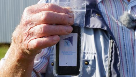 Ein Mann hält einen Pager in der Hand.