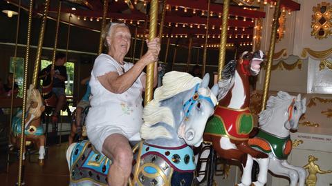Eine alte Frau sitzt auf einer Pferdefigur in einem Kinderkarussell.