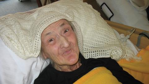 Eine alte Frau blickt verschmitzt in die Kamera, ein Häkeldeckchen auf dem Kopf.