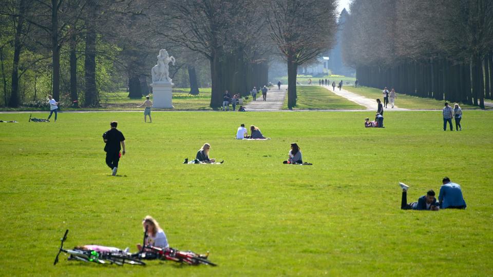 In gebührendem Abstand zueinander genießen Menschen das Frühlingswetter auf der Karlswiese in der Kasseler Aue.