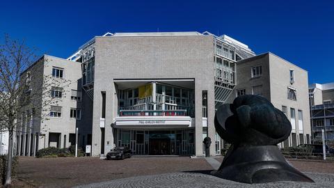Ein Bürogebäude, das Paul-Ehrlich-Institut in Langen, im Vordergrund eine schwarze Skulptur