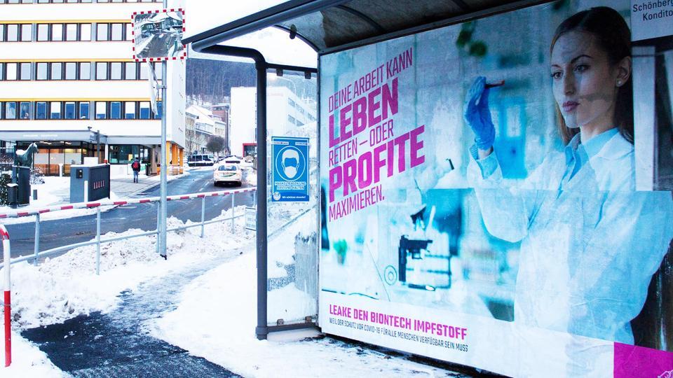 """Ein Bushaltestellen-Plakat mit der Aufschrift """"Deine Arbeit kann Leben retten - oder Profite maximieren"""" vor einem Firmengelände."""