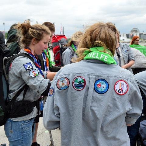 Eine Gruppe von Pfadfinderinnen und Pfadfindern steht in Uniform auf dem Berliner Bahnhofsvorplatz.