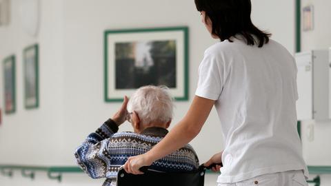 Eine Altenpflegerin schiebt einen Bewohner im Rollstuhl durch ein Altenheim