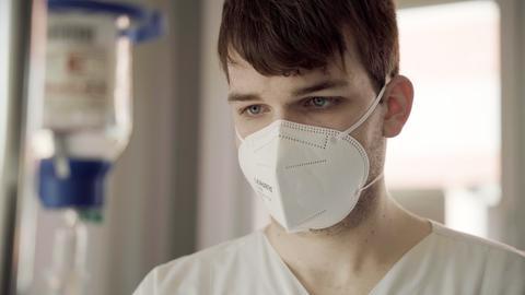 Pfleger Alexander Riedel mit Maske an seinem Arbeitsplatz
