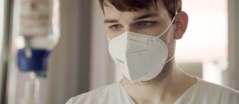 Kopf von Alexander Riede, derl steht mit Maske scheinbar an einem Bett steht. Neben seinem Gesicht ist leicht verschwommen ein Tropf zu sehen.